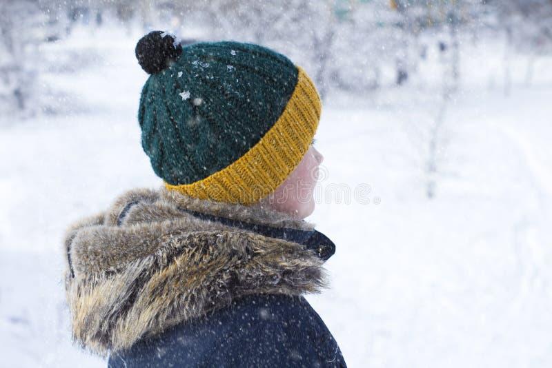 Junge in einem Hut mit einem Bubo draußen im Winter lizenzfreie stockbilder