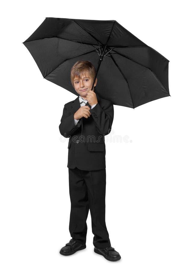 Junge in einem Smoking, unter einem Regenschirm. stockfotos