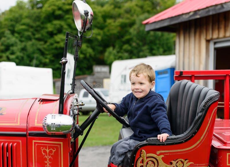 Junge in einem Weinlese-Löschfahrzeug-Lächeln stockbild
