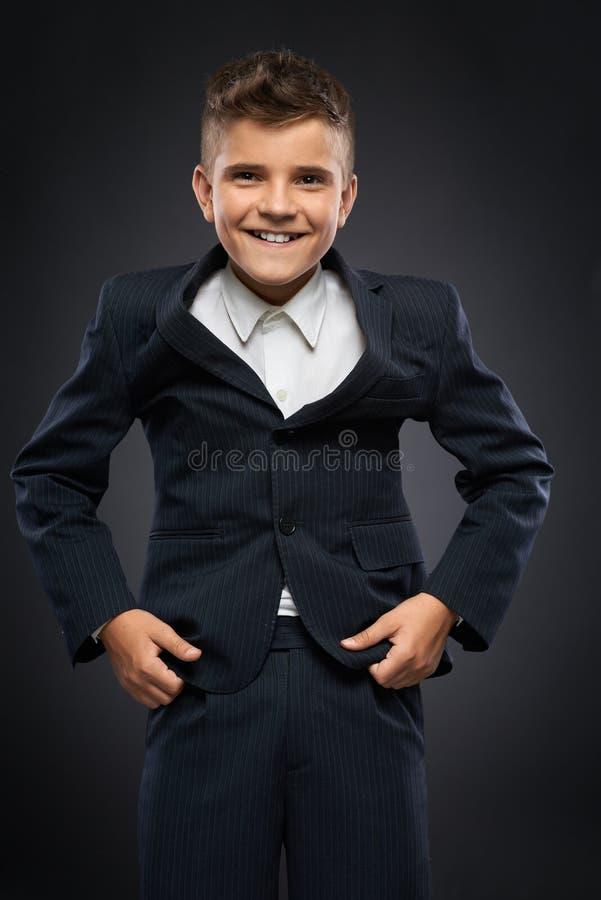 Junge in einer schwarzen Anzugsjacke korrigiert stockbilder