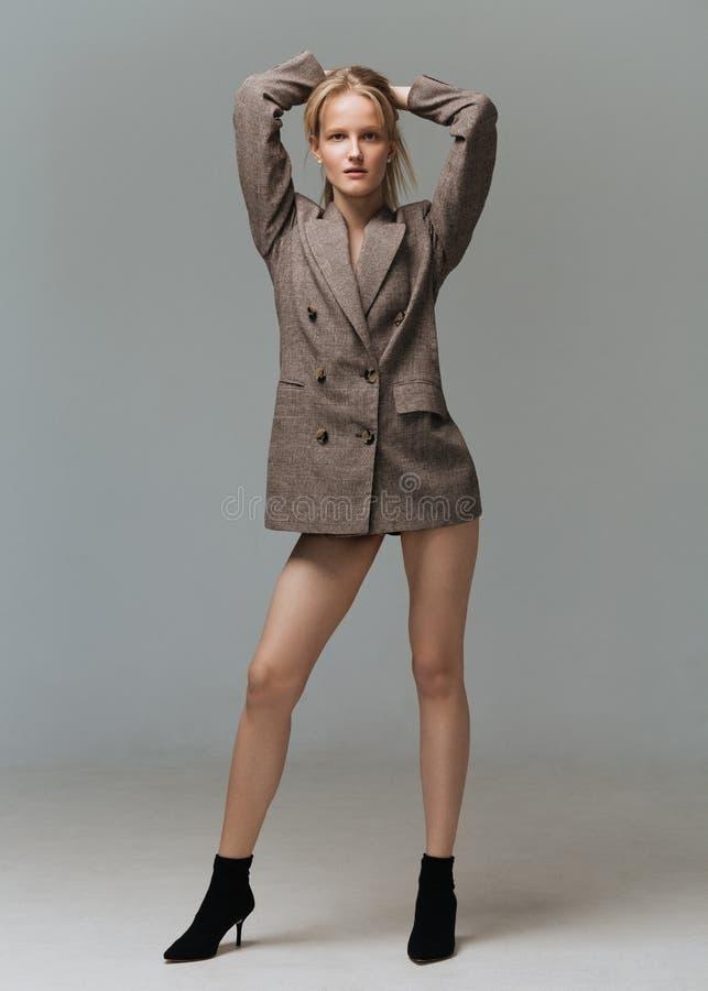 Junge elegante Frau der Ganzaufnahme in der braunen Jacke lizenzfreies stockbild