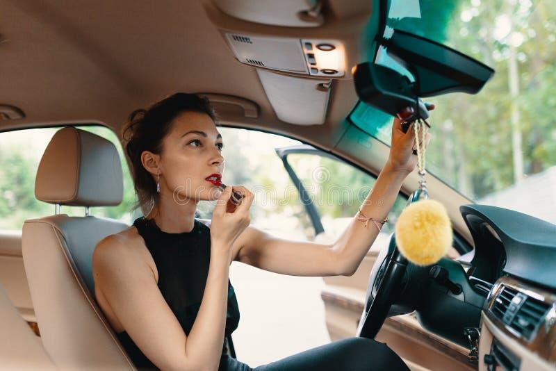 Junge elegante Frau, die im Autoansichtspiegel beim Anwenden des Makes-up, Lippenstift auf den Lippen schaut stockbild