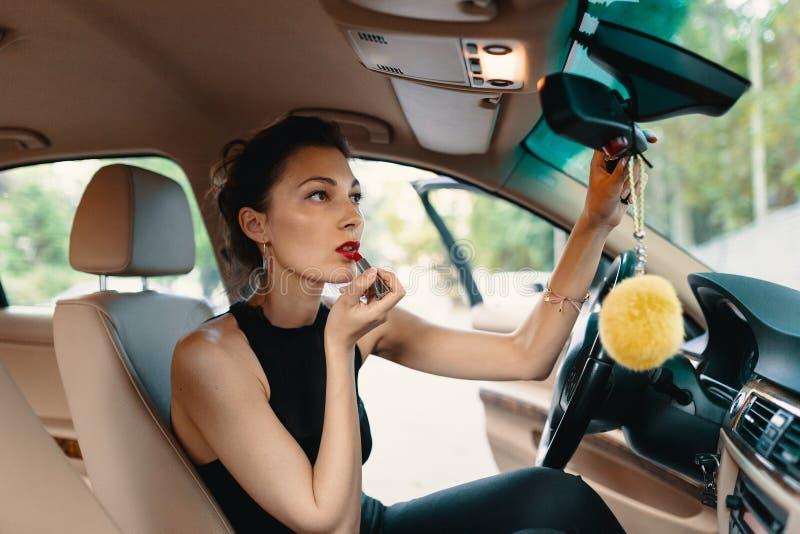 Junge elegante Frau, die im Autoansichtspiegel beim Anwenden des Makes-up, Lippenstift auf den Lippen schaut stockfotografie