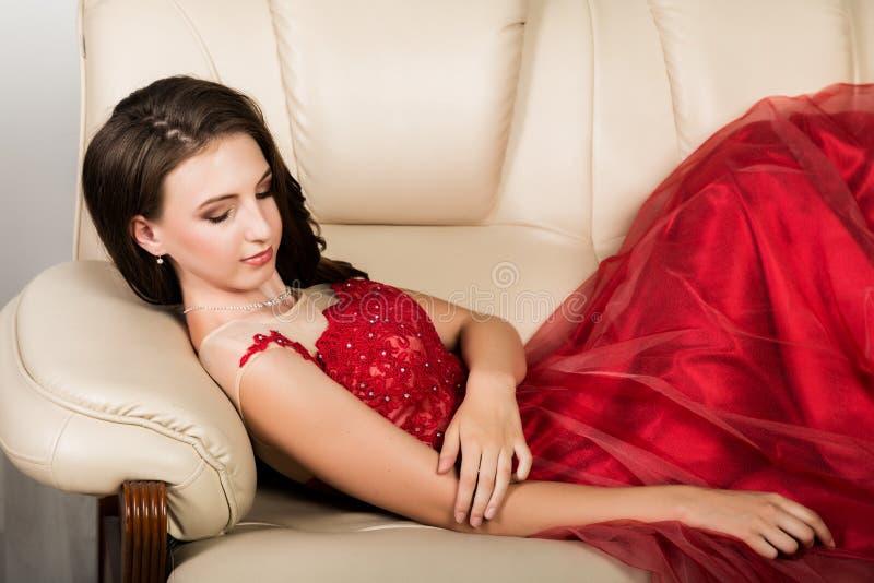 Junge elegante Frau mit Berufsfrisur im langen roten Kleid stand auf Sofa still lizenzfreie stockbilder