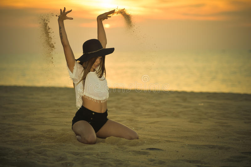 Junge elegante hübsche Dame mit einem Hut auf dem Hintergrund der Stranddämmerung draußen, Porträt lizenzfreies stockfoto