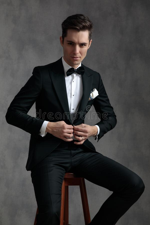 Junge, elegante Männer, die Tuxedo tragen und das Fell anordnen stockfotografie