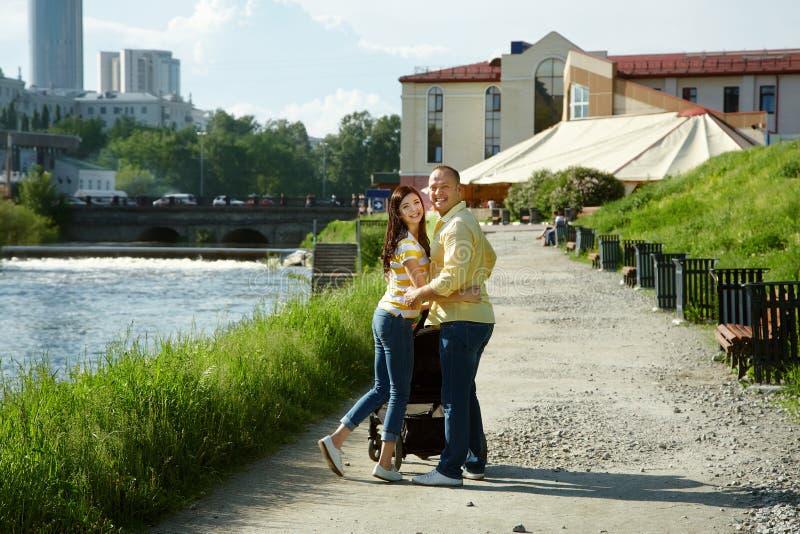 Junge Eltern für einen Weg mit Spaziergänger lizenzfreie stockfotos
