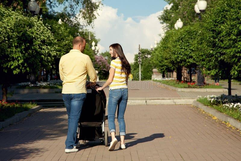 Junge Eltern für einen Weg mit Spaziergänger stockbilder