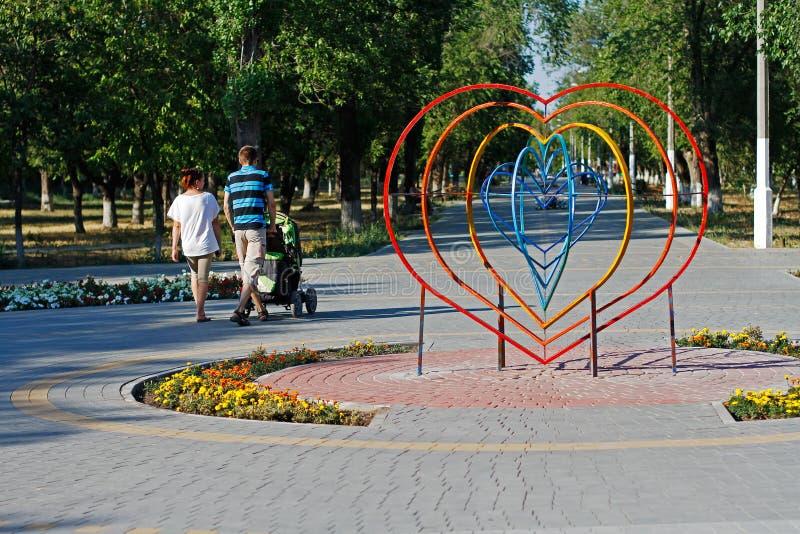 Junge Eltern gehen nahe bei einer Installation in Form eines Herzens im Park in Wolgograd stockfotos