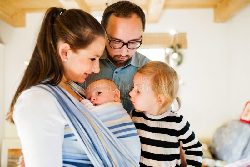 Junge Eltern mit zwei Kindern zur Weihnachtszeit lizenzfreie stockbilder
