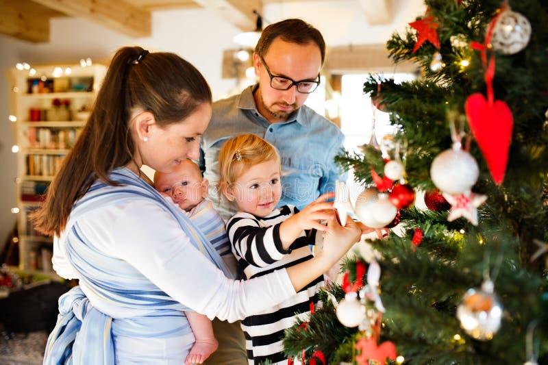 Junge Eltern mit zwei Kindern zur Weihnachtszeit lizenzfreies stockfoto