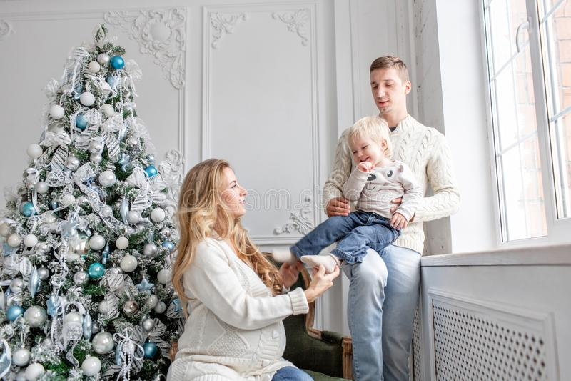 Junge Eltern täuschen herum und spielen mit kleinem Sohn Glückliche Familie, die Spaß zu Hause hat Weihnachtsmorgen im hellen Leb stockfoto
