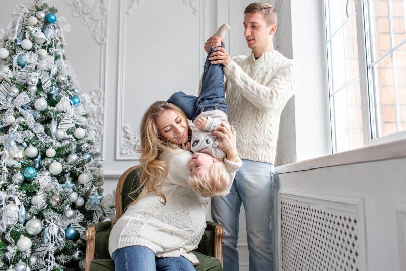 Junge Eltern täuschen herum und spielen mit kleinem Sohn Glückliche Familie, die Spaß zu Hause hat Weihnachtsmorgen im hellen Leb stockbilder