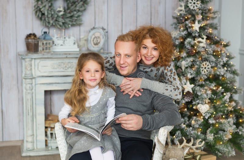 Junge Eltern und ihre Tochter sitzen und lesen nahe Weihnachtsbaum lizenzfreie stockbilder