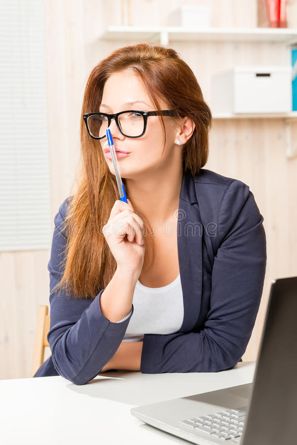 Junge Empfangsdame, die hinter einem Schreibtisch in einem Büro sitzt lizenzfreie stockfotografie