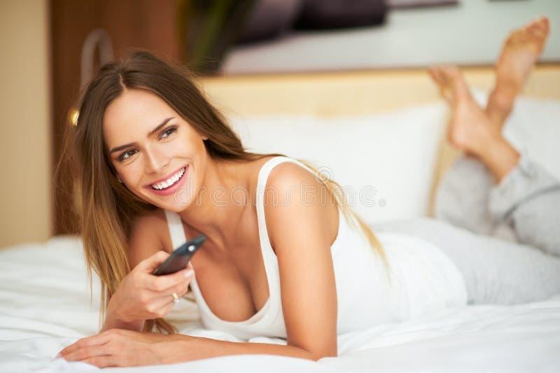 Junge empfindliche Schönheit, die auf ein Bett mit Fernbedienung legt stockfoto