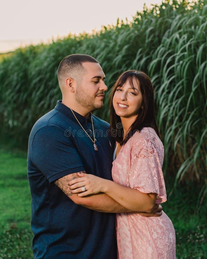Junge engagierte Paare außerhalb des Küssens bei Sonnenuntergang lizenzfreie stockfotos