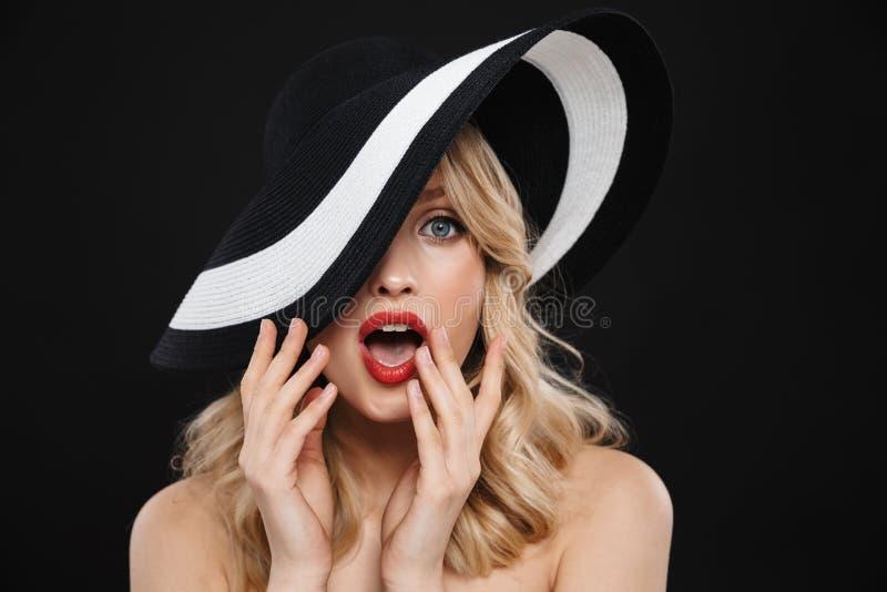 Junge entsetzte Blondine mit der roten Aufstellung des hellen Makes-up Lippenlokalisiert über tragendem Hut des schwarzen Wandhin lizenzfreie stockbilder