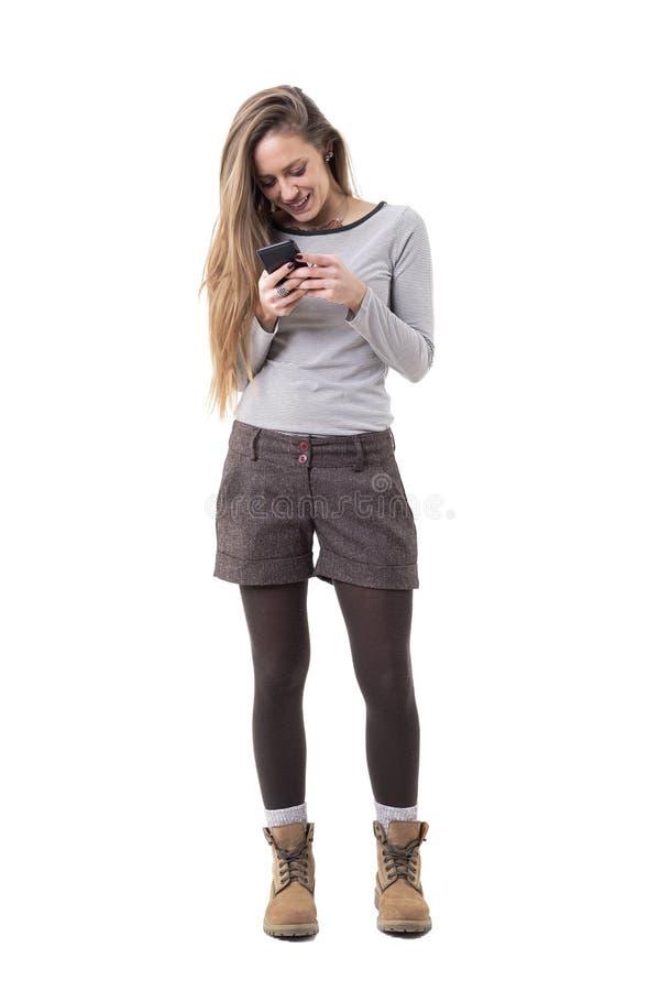 Junge entspannte Schönheit in surfendem Internet der alternativen Artkleidungs am intelligenten Telefon lizenzfreie stockbilder