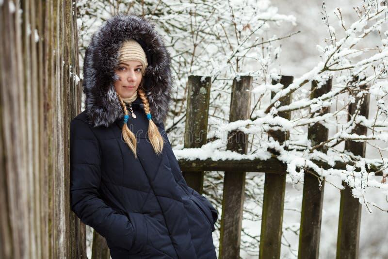 Junge entzückende Frau, die den blauen mit Kapuze Mantel genießt in Winterwald draußen schlendern trägt Jahreszeit-Frischekonzept lizenzfreie stockfotografie