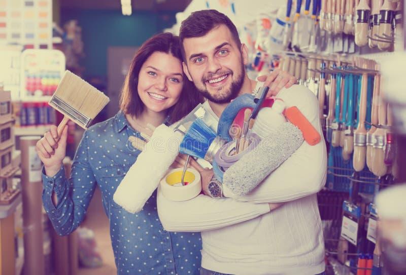 Junge erfüllte Paare, die Werkzeuge für die Hauserneuerung zeigen lizenzfreies stockfoto