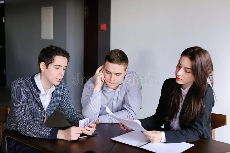 Junge erfolgreiche Banker zwei Kerle und Mädchen überprüfen und stimmen Dokument zu stockbilder