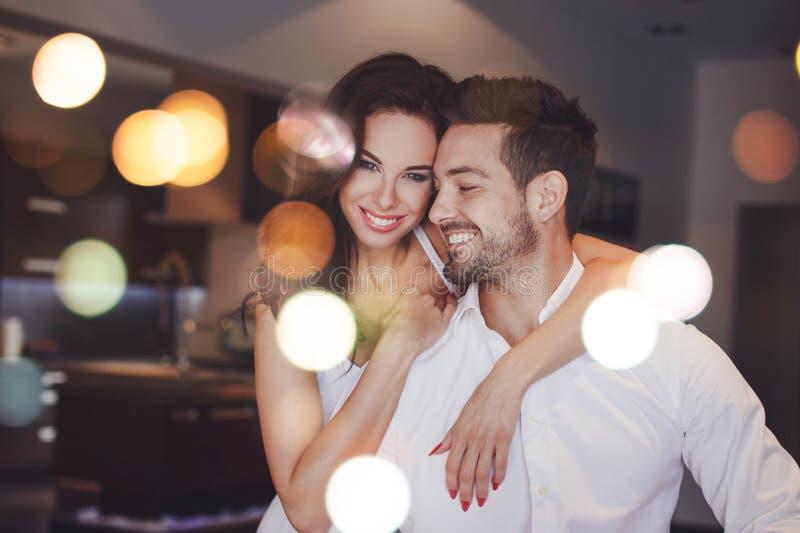 Junge erfolgreiche zuhause lächelnde Paare, Frauenumarmungsmann, boke lizenzfreie stockfotos