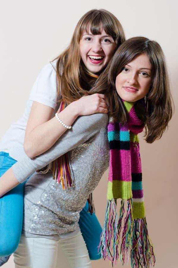 2 junge erfreuliche hübsche Frauen, die umarmende des Spaßes freundliche und reitene glückliche lächelnde u. schauende Kamera hab lizenzfreie stockbilder