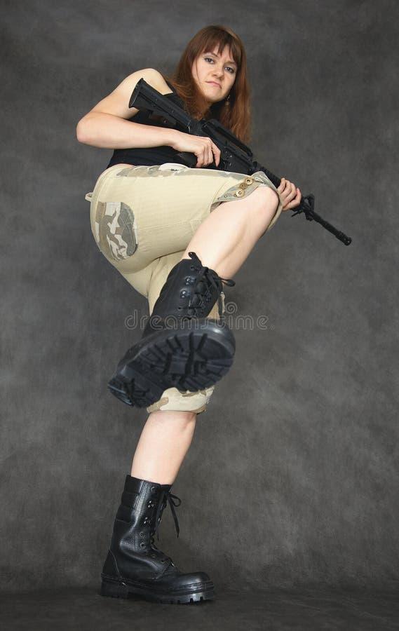 Junge ernste Frau, bewaffnet mit dem Gewehr, tretend stockfoto