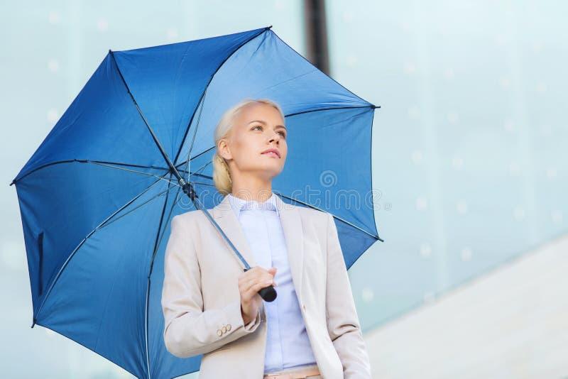 Junge ernste Geschäftsfrau mit Regenschirm draußen stockfotografie