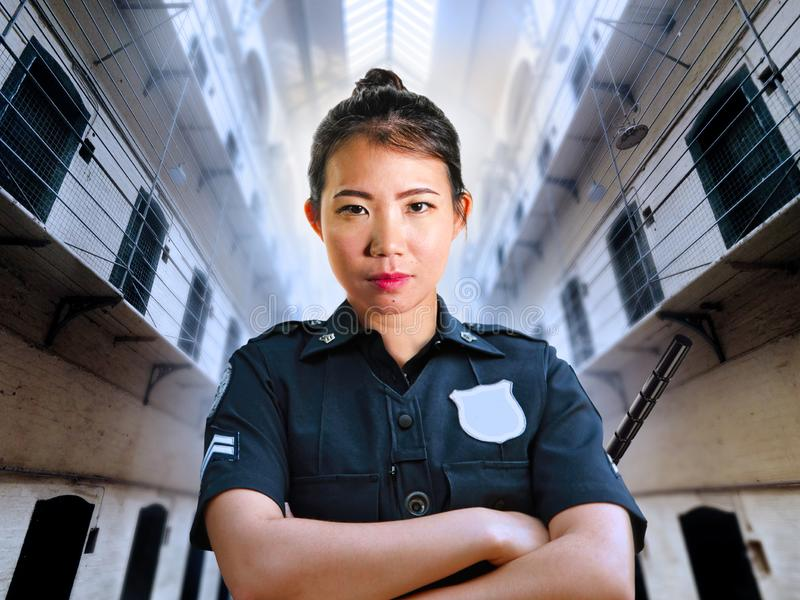 Junge ernste und attraktive asiatische chinesische Schutzfrauenstellung an tragender Polizeiuniform der Staatsgefängnisgefängnish stockfotos