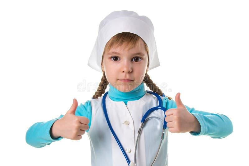 Junge ernste weibliche Krankenschwester, tragende Uniform und Stethoskop, mit dem Daumen herauf Finger, ausgezeichnetes Zeichen lizenzfreie stockbilder