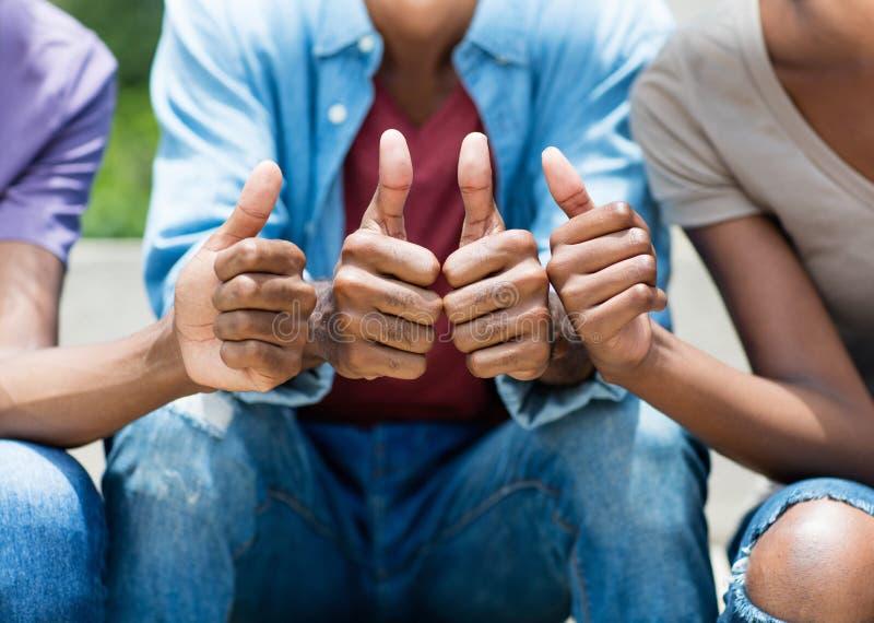 Junge Erwachsene des Afroamerikaners, die sich Daumen zeigen lizenzfreie stockbilder