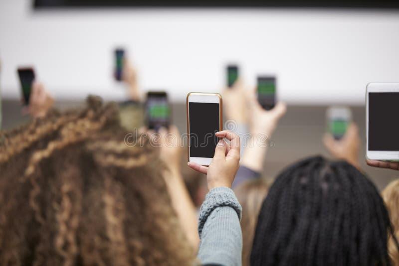 Junge Erwachsene, die Fotos mit Telefonen, hinterer Ansichtabschluß oben machen lizenzfreies stockbild
