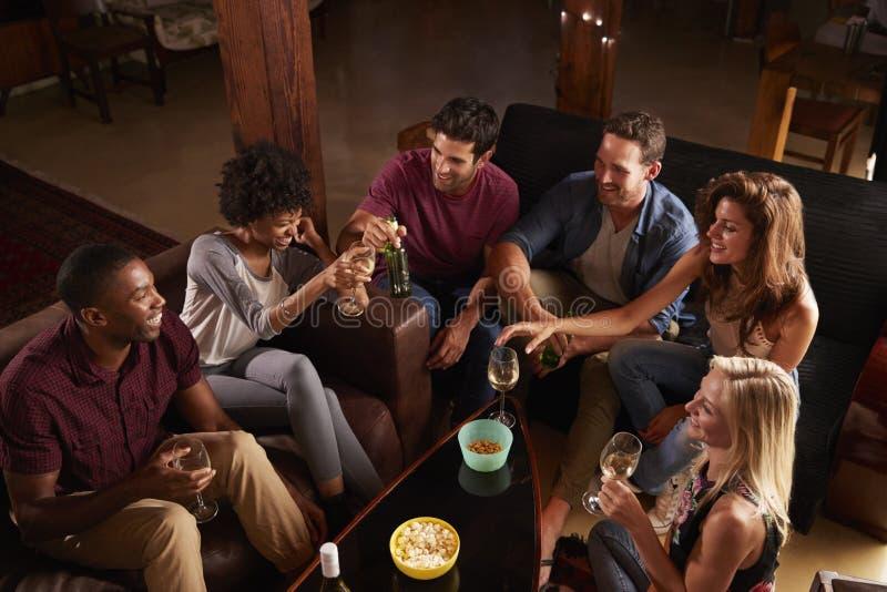 Junge Erwachsene, die zu Hause an einer Partei, erhöhte Ansicht gesellig sind stockfotografie