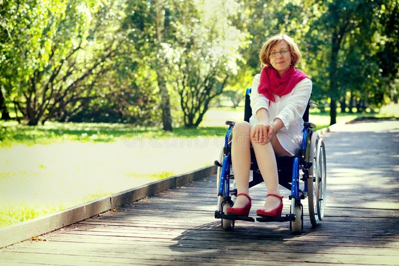 Junge erwachsene Frau auf Rollstuhl im Park lizenzfreie stockfotografie