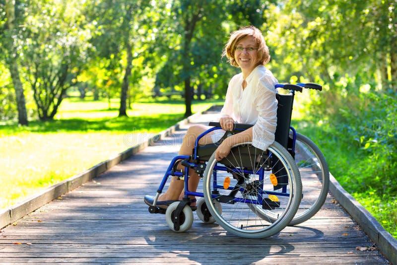 Junge erwachsene Frau auf Rollstuhl im Park stockbilder