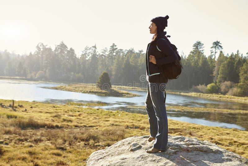 Junge erwachsene Frau, die allein auf einem Felsen in der Landschaft steht stockbild
