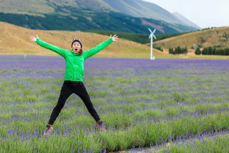 Junge erwachsene Frau, die auf Lavendelfeld springt stockfoto