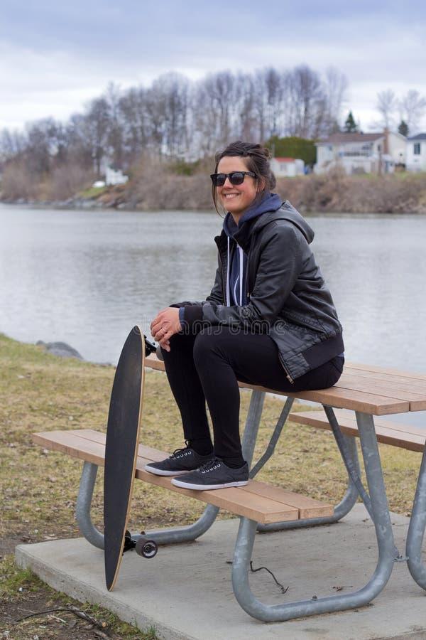 Junge erwachsene Frau, die mit longboard sich entspannt lizenzfreies stockfoto