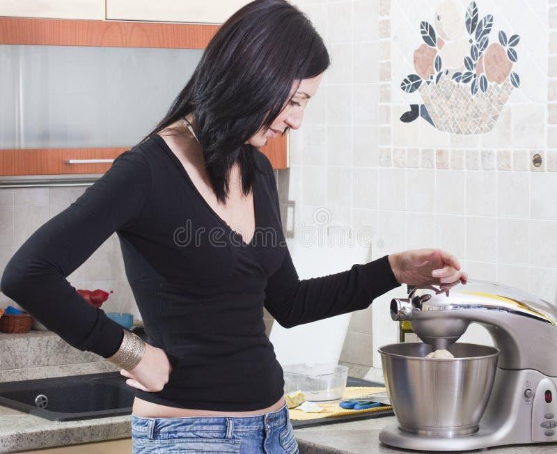 Junge erwachsene Frau, die zu Hause kocht stockbilder
