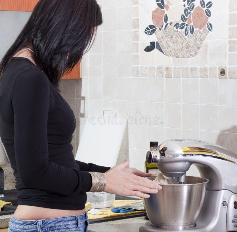 Junge erwachsene Frau, die zu Hause kocht stockbild