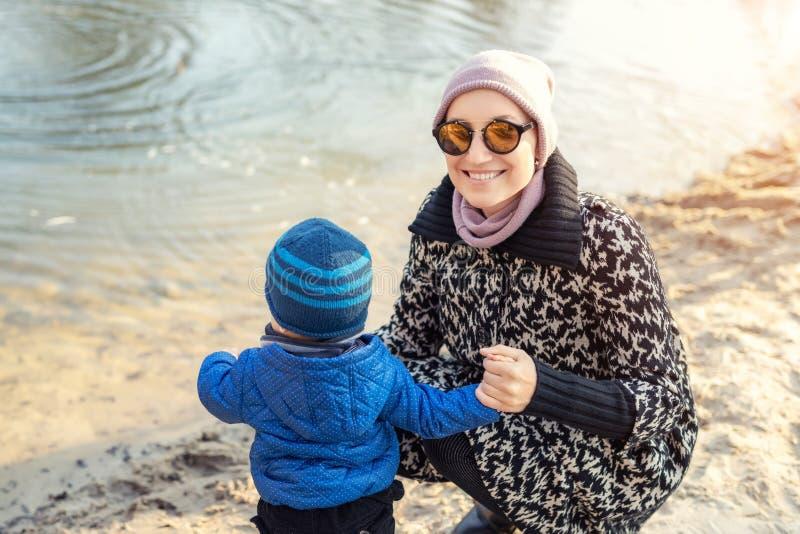 Junge erwachsene Frau mit dem netten Kleinkindjungen, der funfeeding Vögel nahe See oder Teich am Stadtpark an hellem atumn Tag h stockfoto