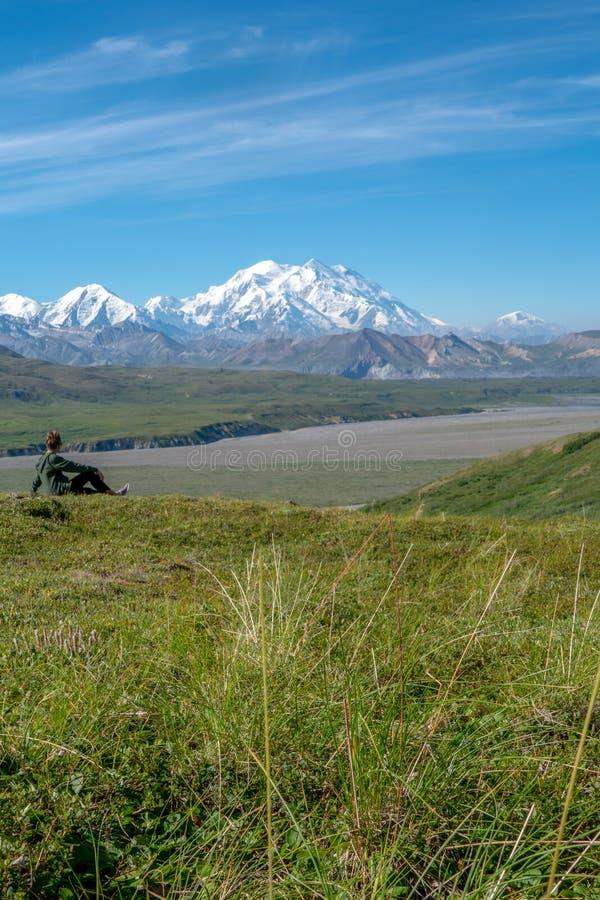 Junge erwachsene Frau sitzt auf einem Hügel, der heraus Berg Denali McKinley in Nationalpark Denali betrachtet Konzept für das De stockfoto