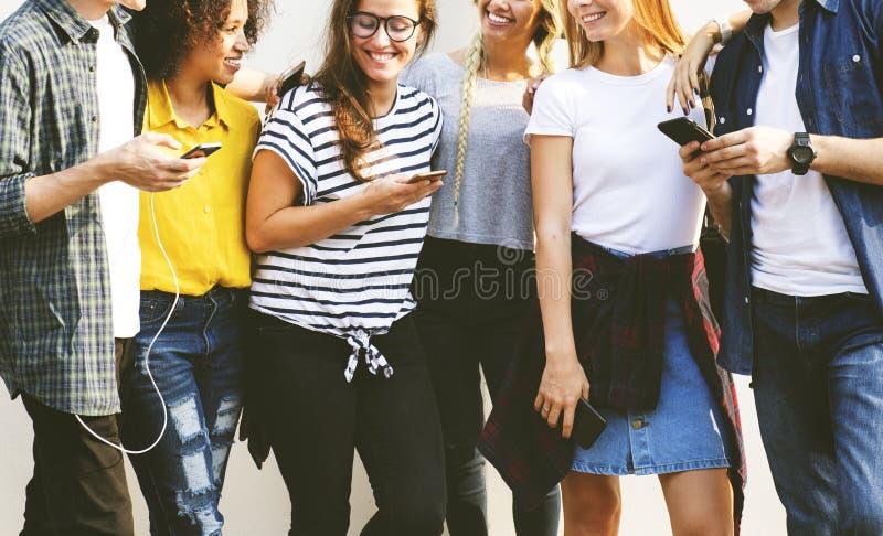 Junge erwachsene Freunde, die zusammen Jugendcu der Smartphones draußen verwenden lizenzfreie stockfotos