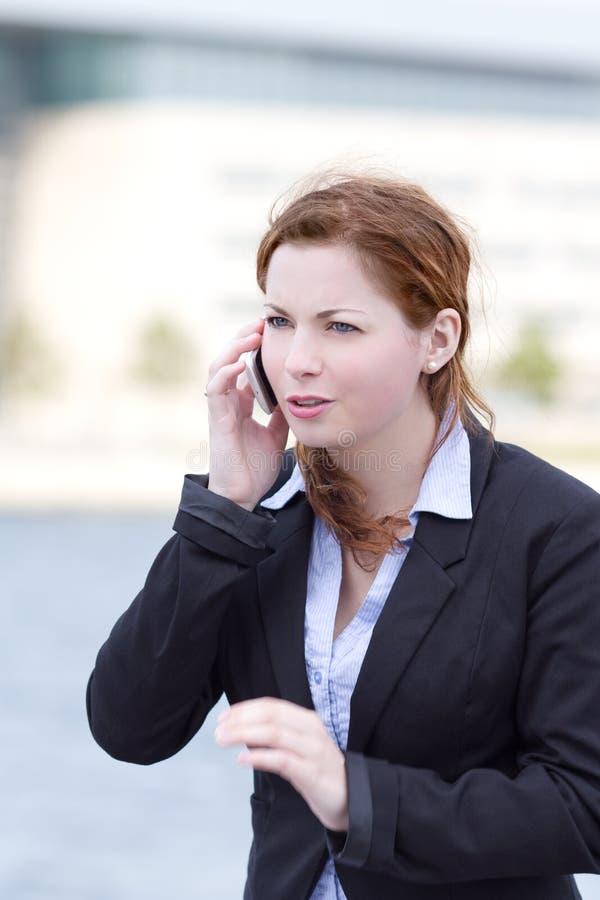 Junge erwachsene Geschäftsfrau, die im intelligenten Telefon spricht stockfoto