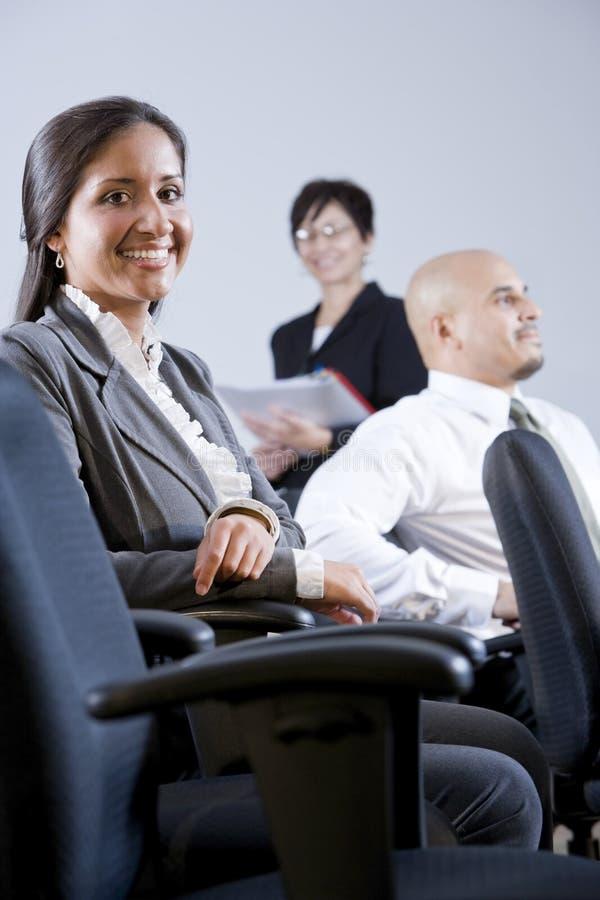 Junge erwachsene hispanische Geschäftsleute in der Sitzung stockfotografie