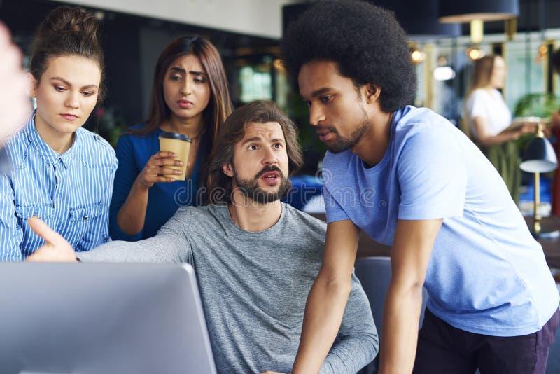 Junge erwachsene Mitarbeiter, die Argumente haben stockbild