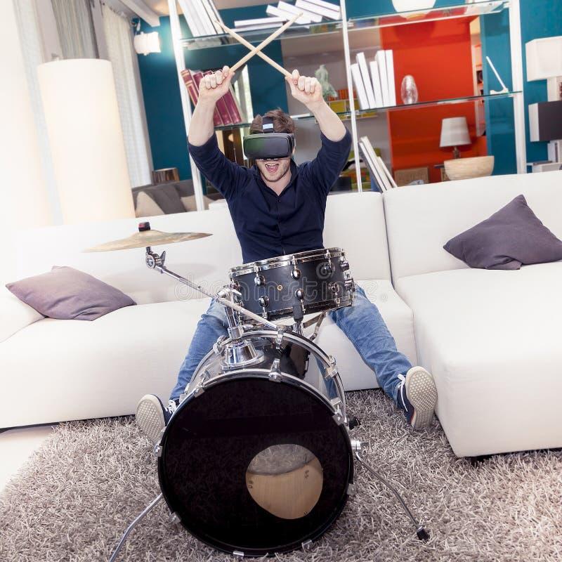 Junge erwachsene spielende Trommeln zu Hause unter Verwendung des Zuschauers für virtuelle Realität lizenzfreie stockfotografie