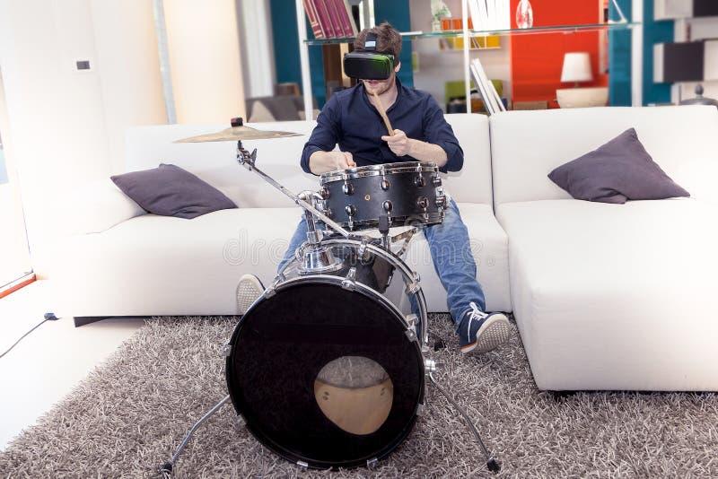 Junge erwachsene spielende Trommeln zu Hause unter Verwendung des Zuschauers für virtuelle Realität stockbild